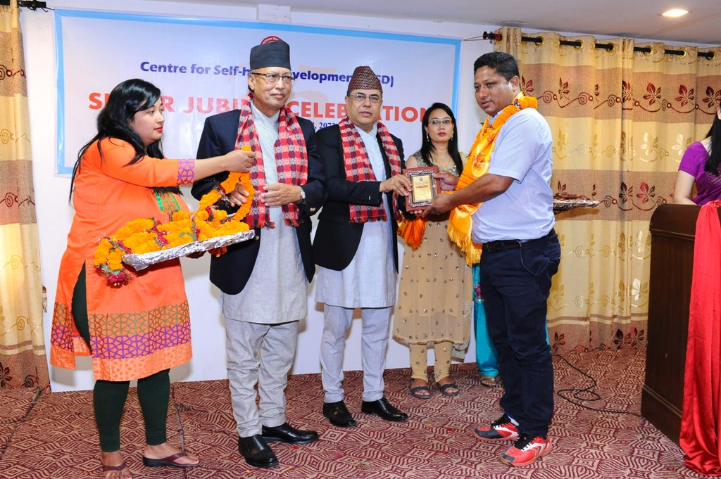 Cheif Guest felicitating Mr. Iswor Lal Rajbhanari, Chairman - DCRDC, Baglung